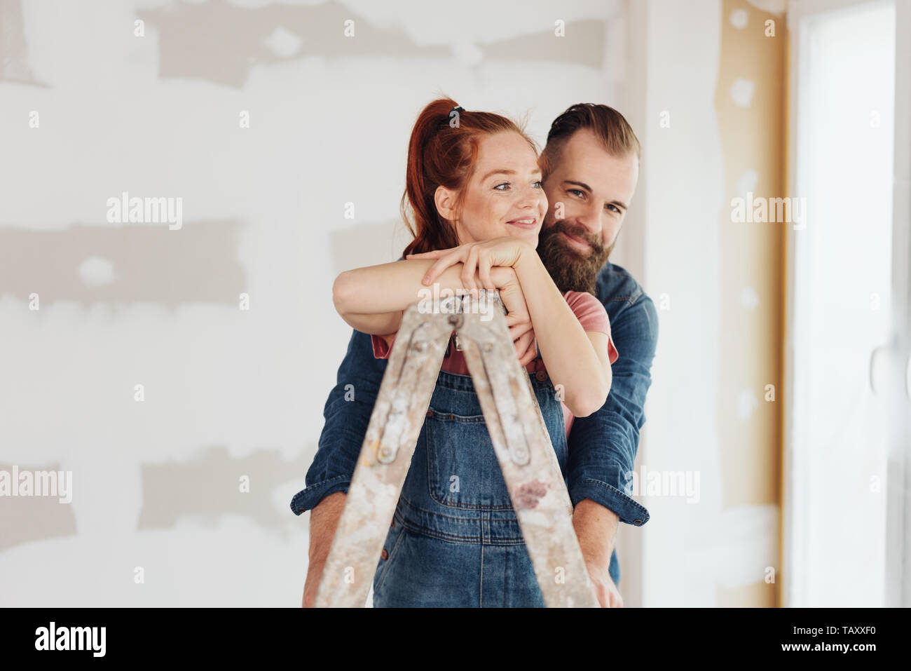 Loving young couple doing DIY home improvements renovating their house standing in an affectionate embrace with the woman leaning on a ladder on site Stock Photo