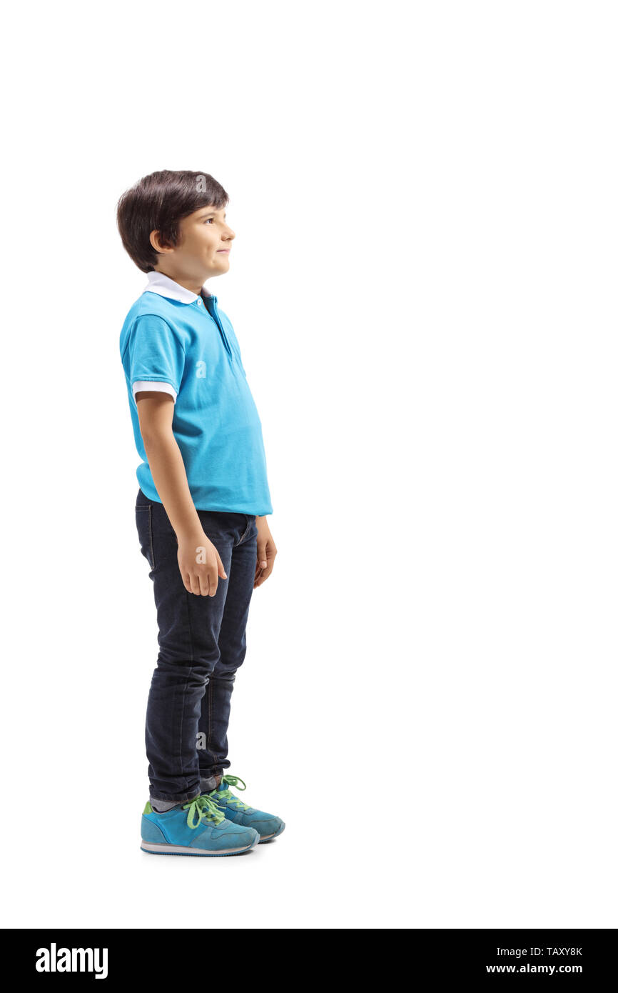 Full length profile shot of a smiling boy standing and waiting isolated on white background - Stock Image