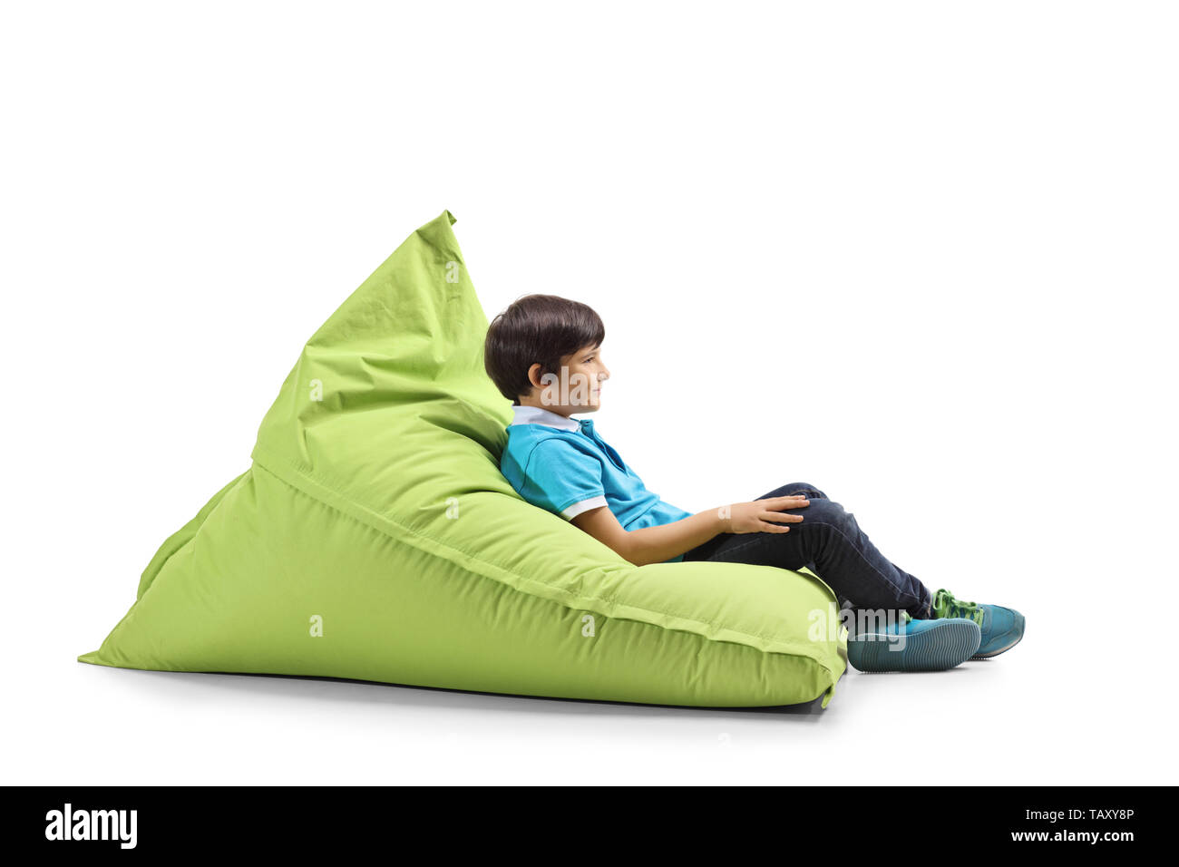 Full length profile shot of a boy relaxing on a green bean bag isolated on white background - Stock Image