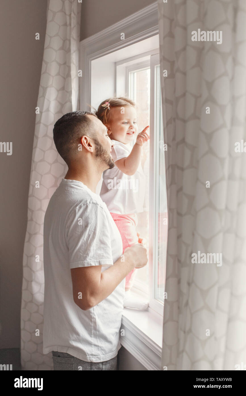 Portrait of Caucasian young father dad with toddler girl daughter looking into window waiting expecting someone. Child staring watching from home outs - Stock Image