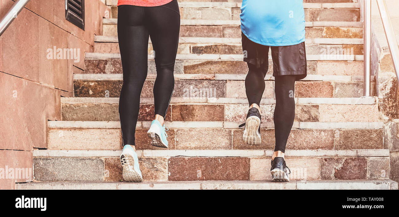 Close up runners legs training outdoor - Young couple doing a workout session on stairs outside - Health people, and sport lifestyle concept - Stock Image