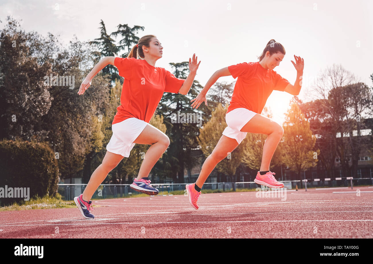 Athletic girls running on competition - Young women doing workout session on track at sunset outdoor - Stock Image