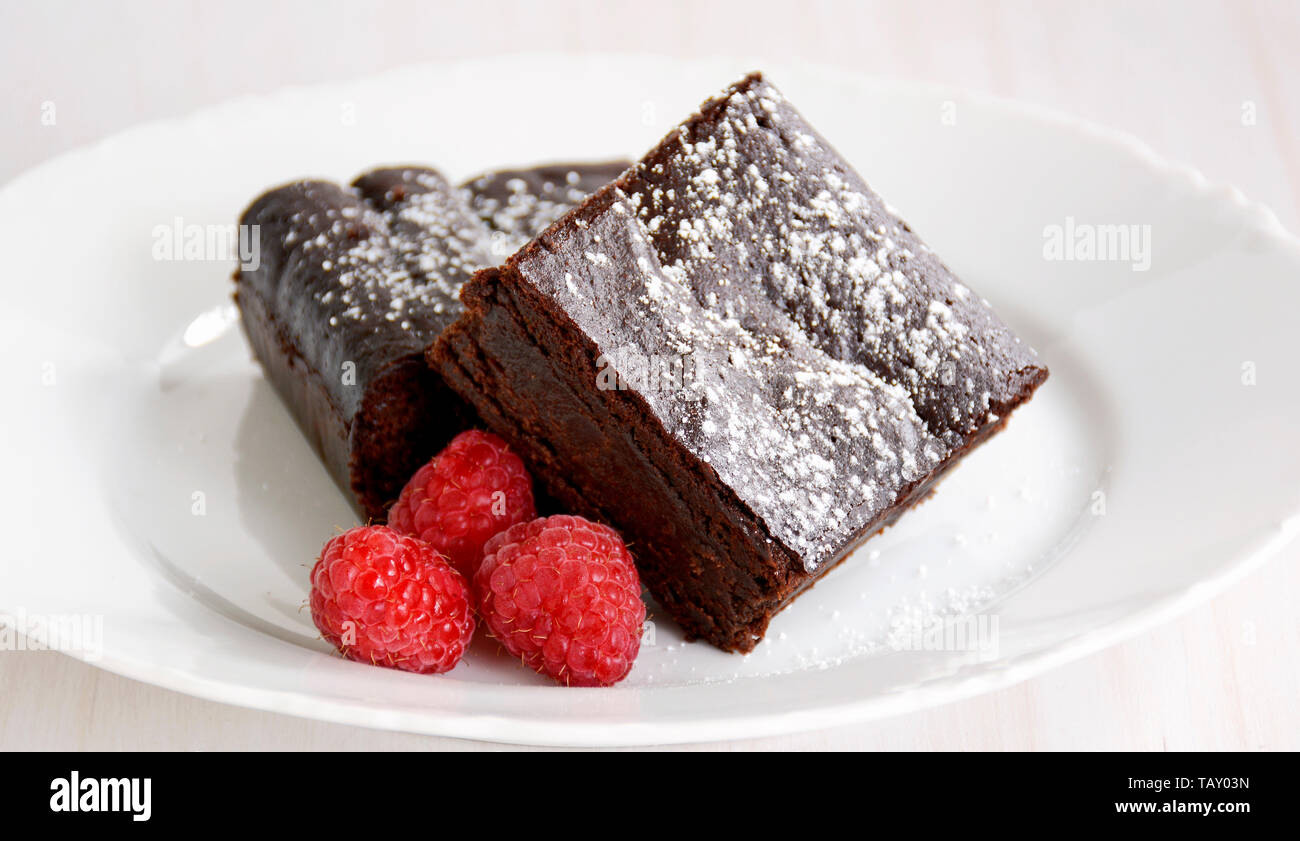 Extremely rich fudgy chocolate brownies made without any grains, totally gluten free. with raspberries. Stock Photo