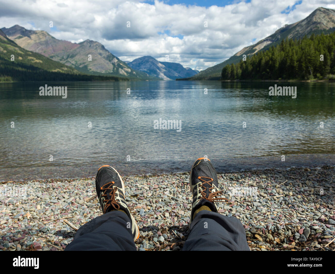 View of a person's feet with a lake and mountain range in the background, Waterton Lake, Waterton-Glacier International Peace Park, Waterton Lakes Nat - Stock Image
