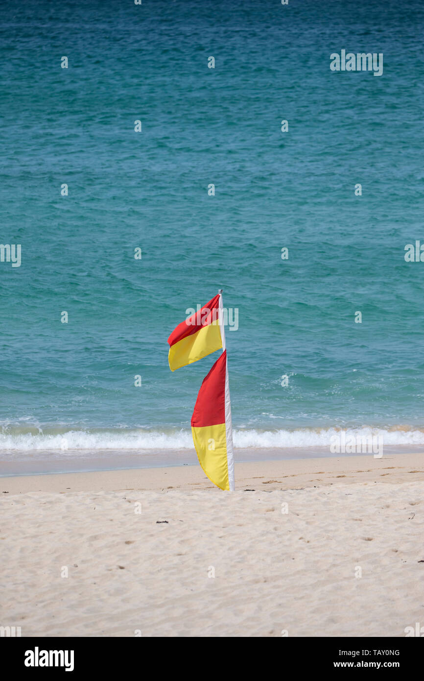 Red and yellow beach warning flags indicating lifeguards are on patrol and an area where it is safe to swim and bathe in the sea - Stock Image