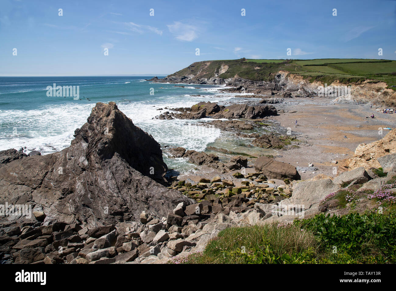 The rugged Cornish coast and Atlantic ocean at Gunwalloe cove on the West of the Lizard peninsula with surfers and holidaymakers - Stock Image