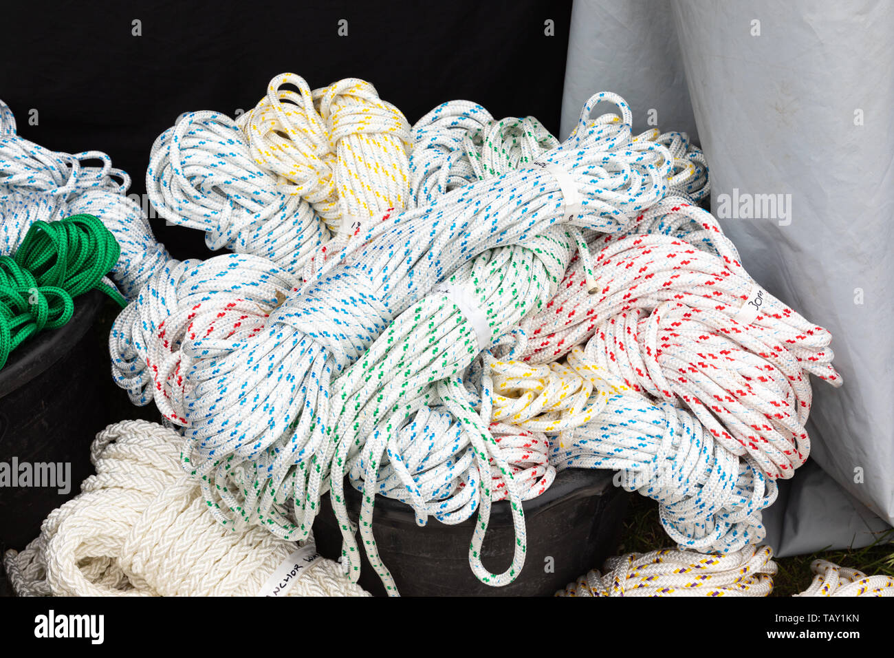 Skeins of white nylon rope with coloured flecks placed haphazardly in a black bucket. - Stock Image