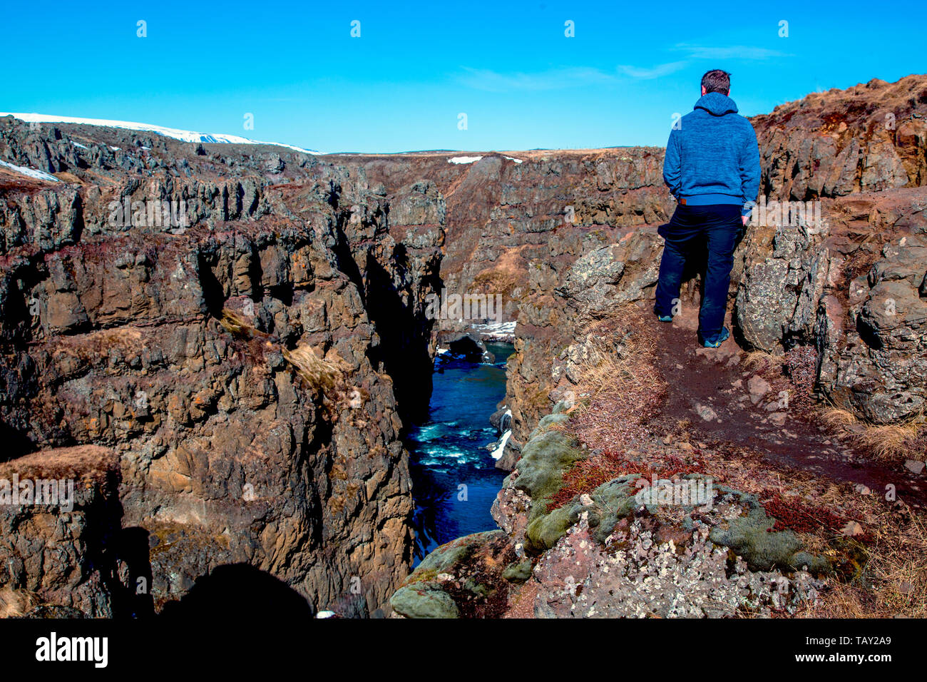 Man looks at a gorge causing a river to flow in the winter of iceland - Stock Image