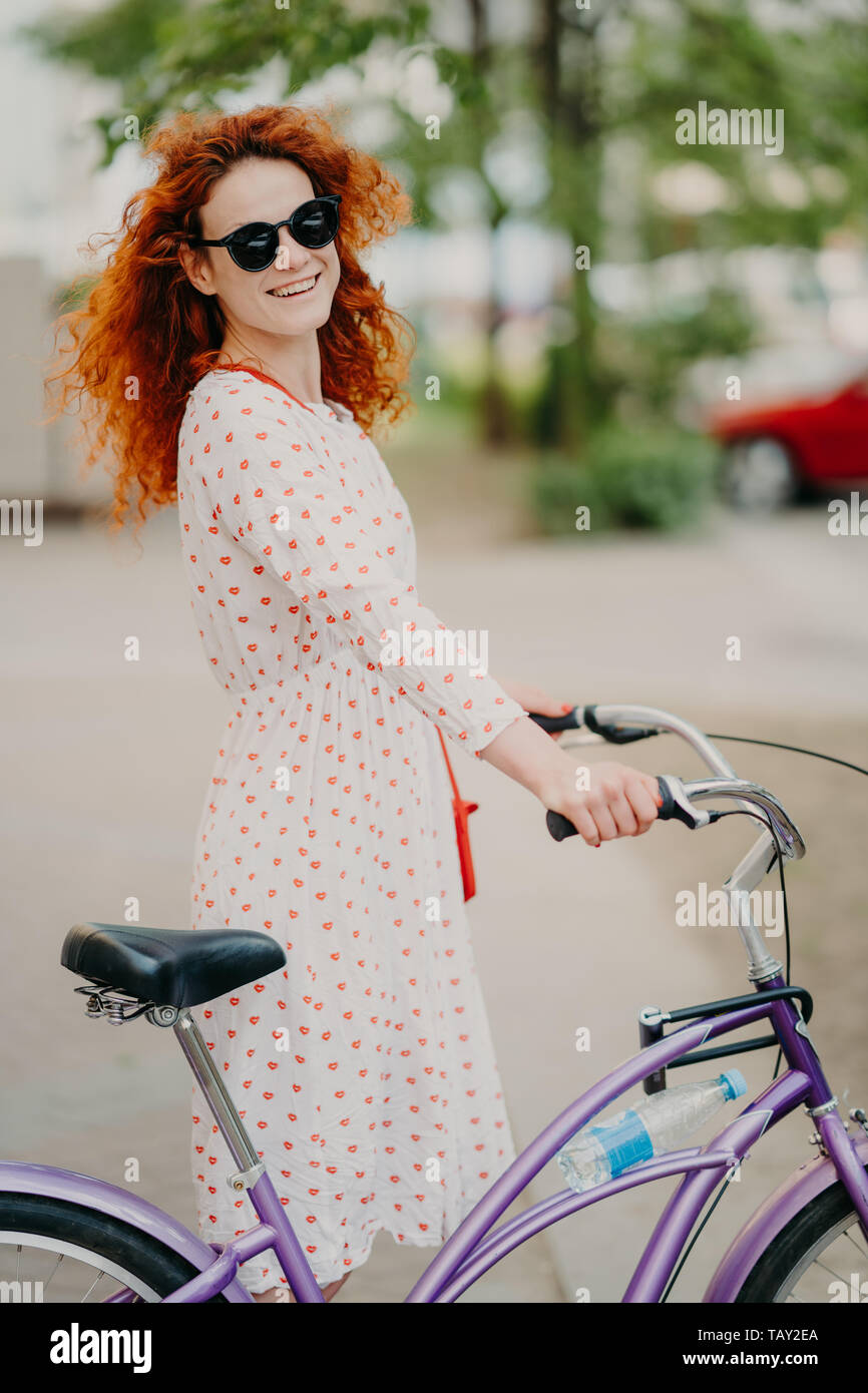 Smiling redhead woman in sunglasses and dress, rides bike through city during summer holidays, has rest or minute break, leads healthy lifestyle, enjo Stock Photo