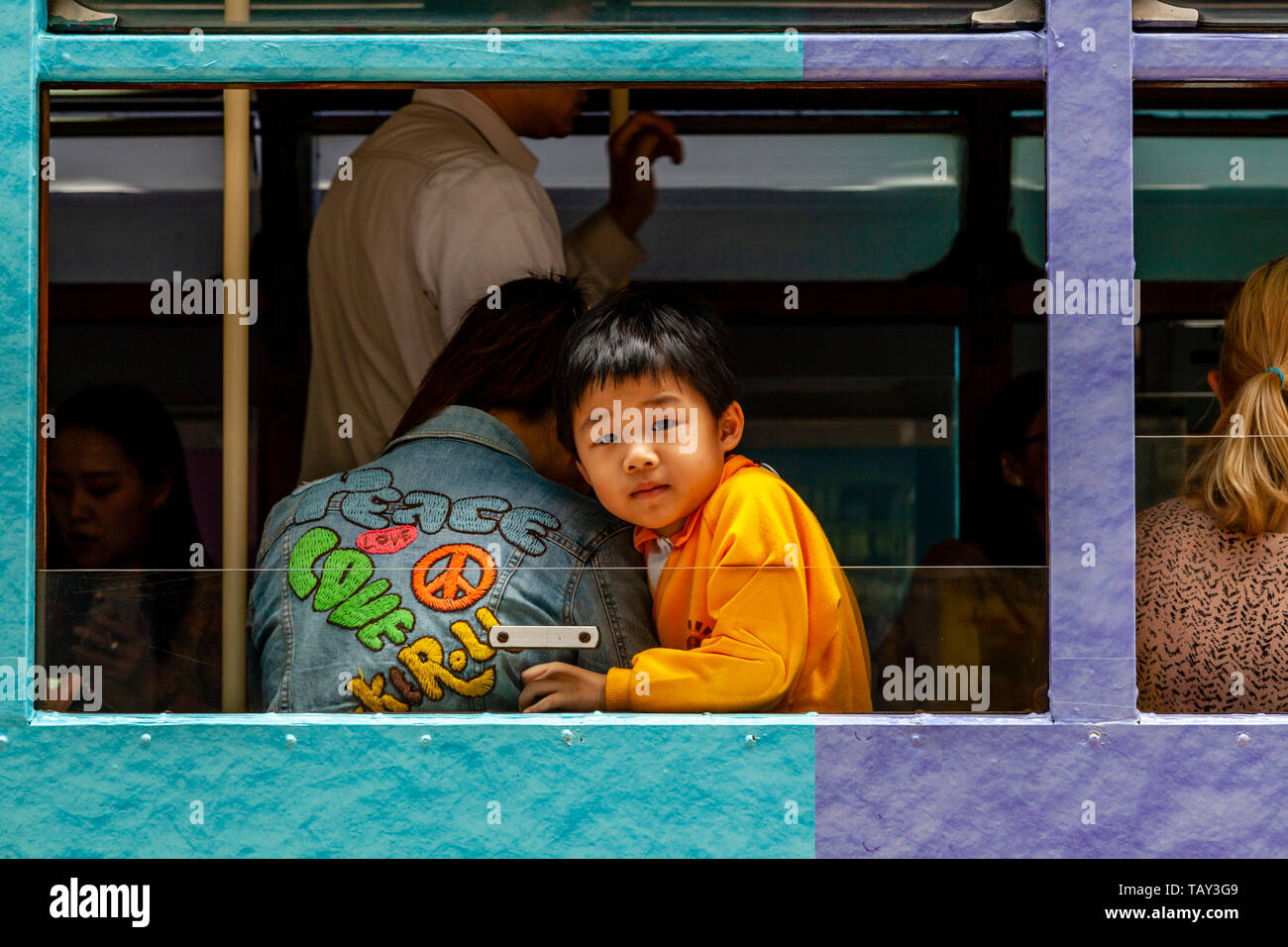 A Young Boy Looks Out Of The Window Of A Traditional Hong Kong Electric Tram, Hong Kong, China - Stock Image