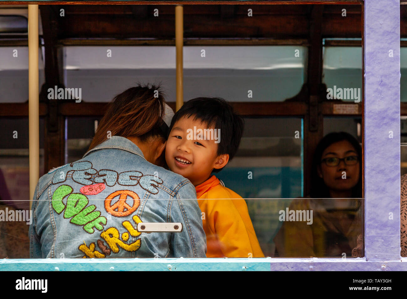 A Young Boy Looks Out The Window Of A Traditional Hong Kong Electric Tram, Hong Kong, China - Stock Image