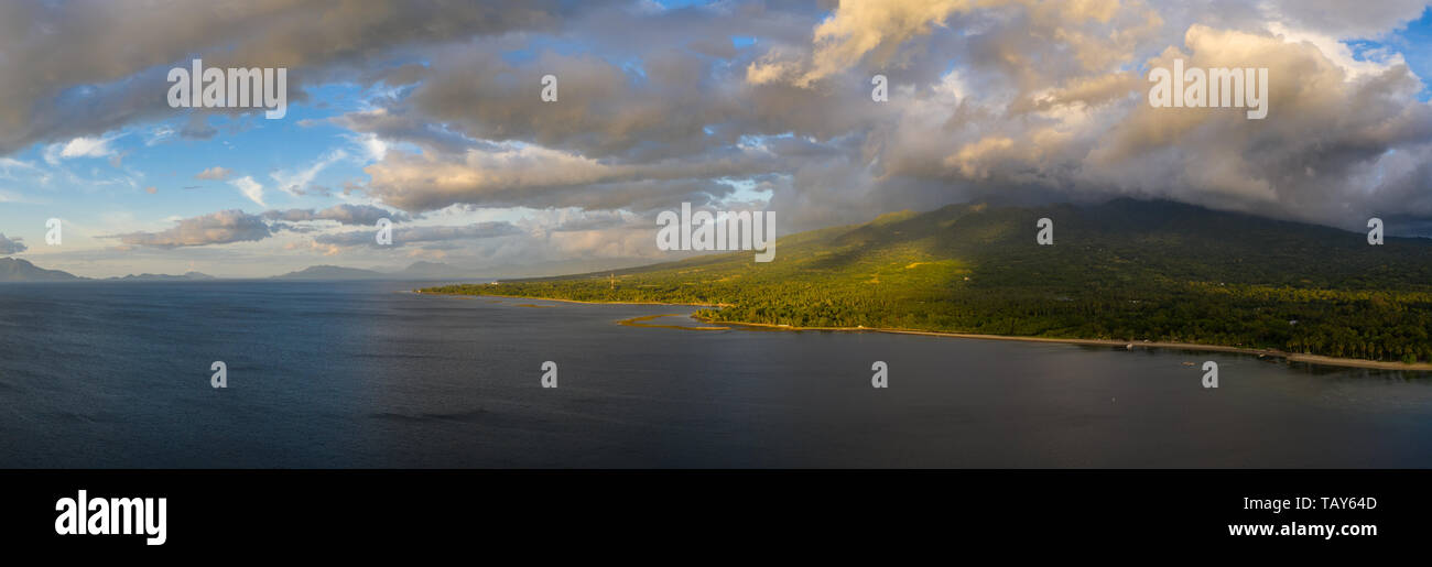 Clouds drift over the scenic coastline of Flores, Indonesia. This large island is surrounded by vibrant coral reefs. Stock Photo