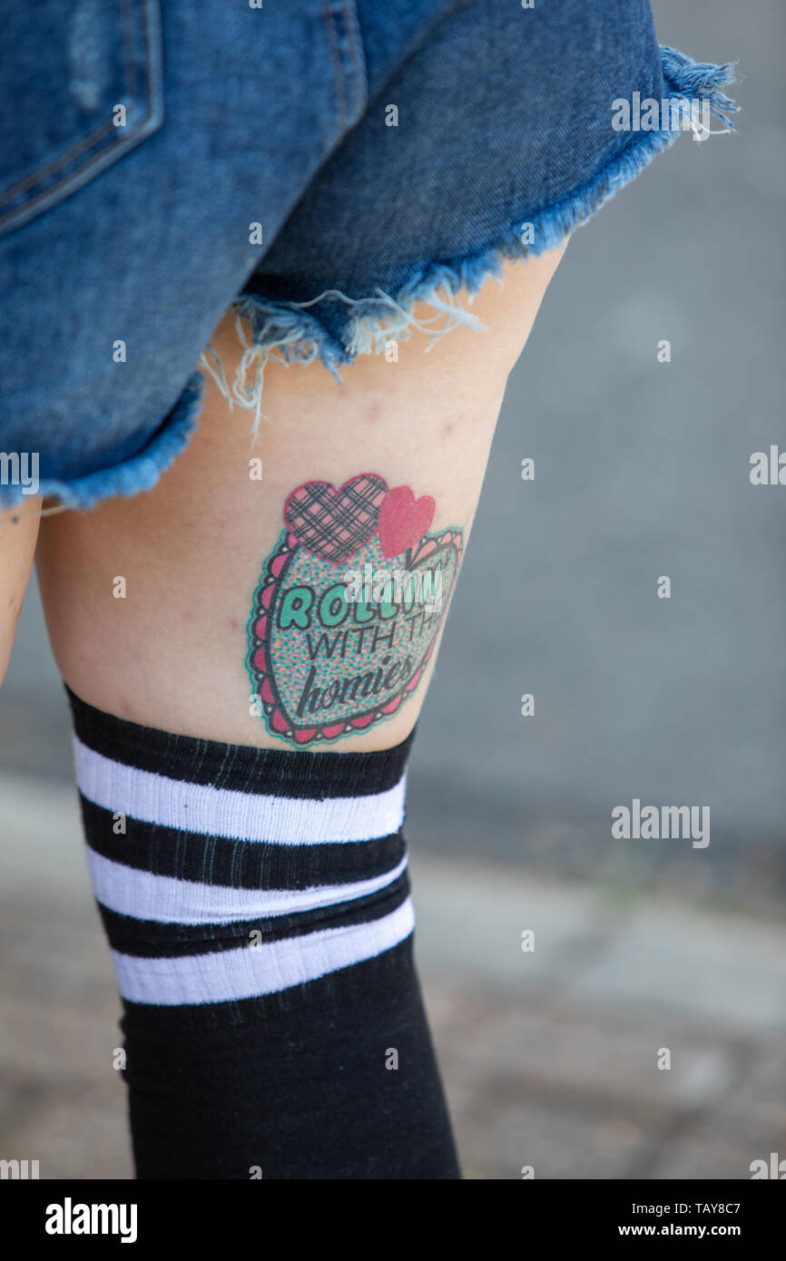 Tattoo thigh of lady with rollin with the homies - Stock Image