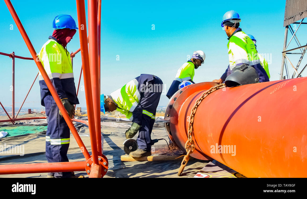 Johannesburg, South Africa - June 09 2010: Tradesman working with an angle grinder on a building site - Stock Image