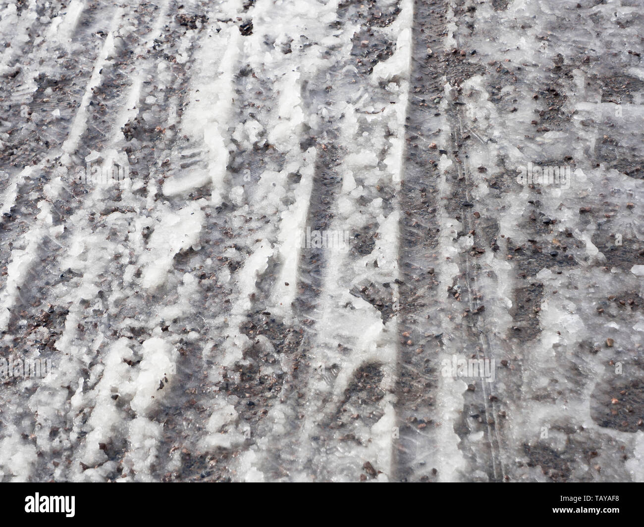 Footprints and bicycle tracks on wet snow is a common surface on the pavements in Oslo Norway in wintertime - Stock Image