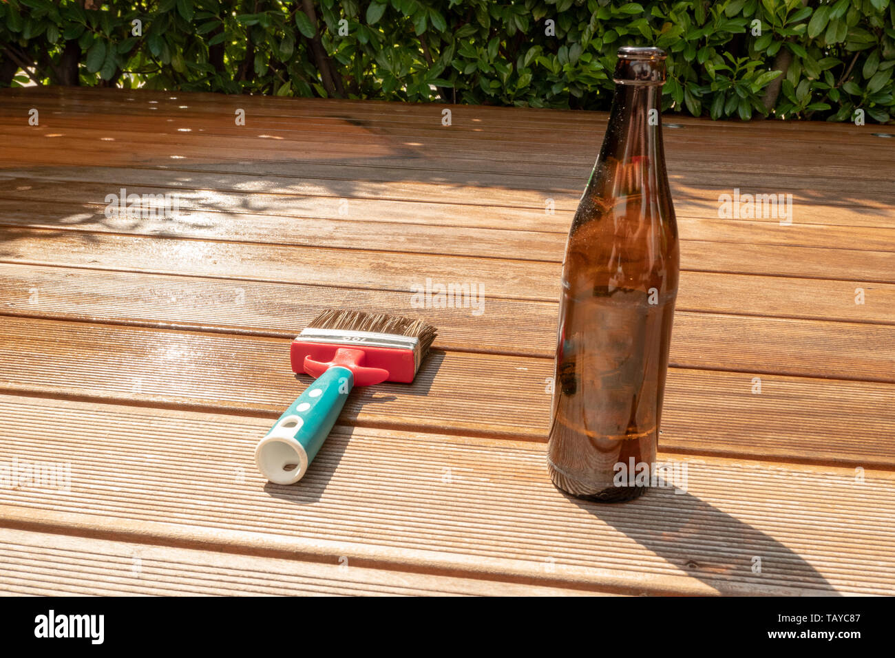empty beer bottle and a brush are lying on the half recessed terrace with glaze - Stock Image