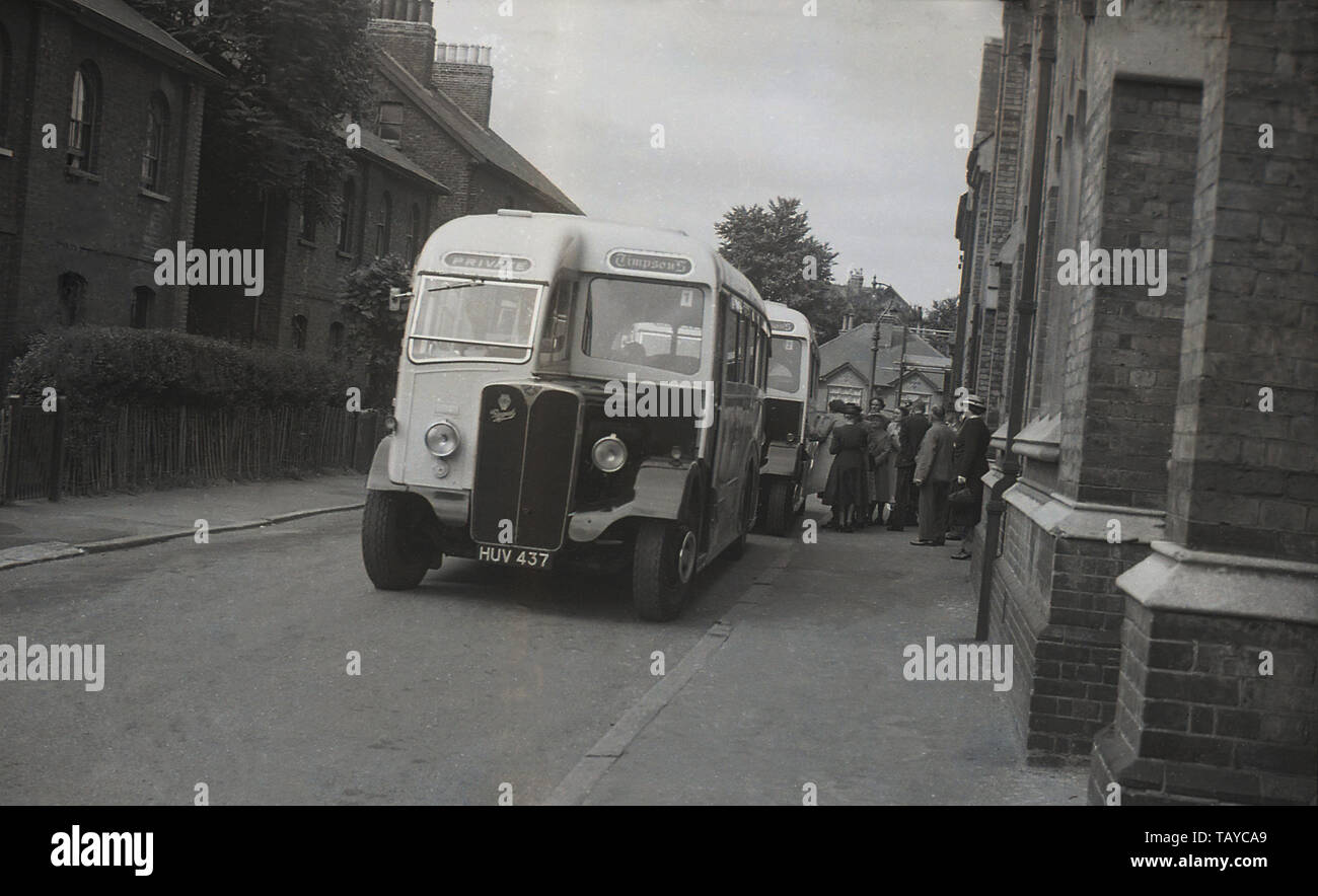 1940s, historical, two Timpson's AEC Regal buses on private hire parked in a narrow urban street picking up passengers in Catford, London, England, UK. Timpson's were the pioneers of the London to Hastings service. The business started by Alexander Timpson in 1912,  lasted up to 1974, wehn National Travel (SE) was formed. - Stock Image