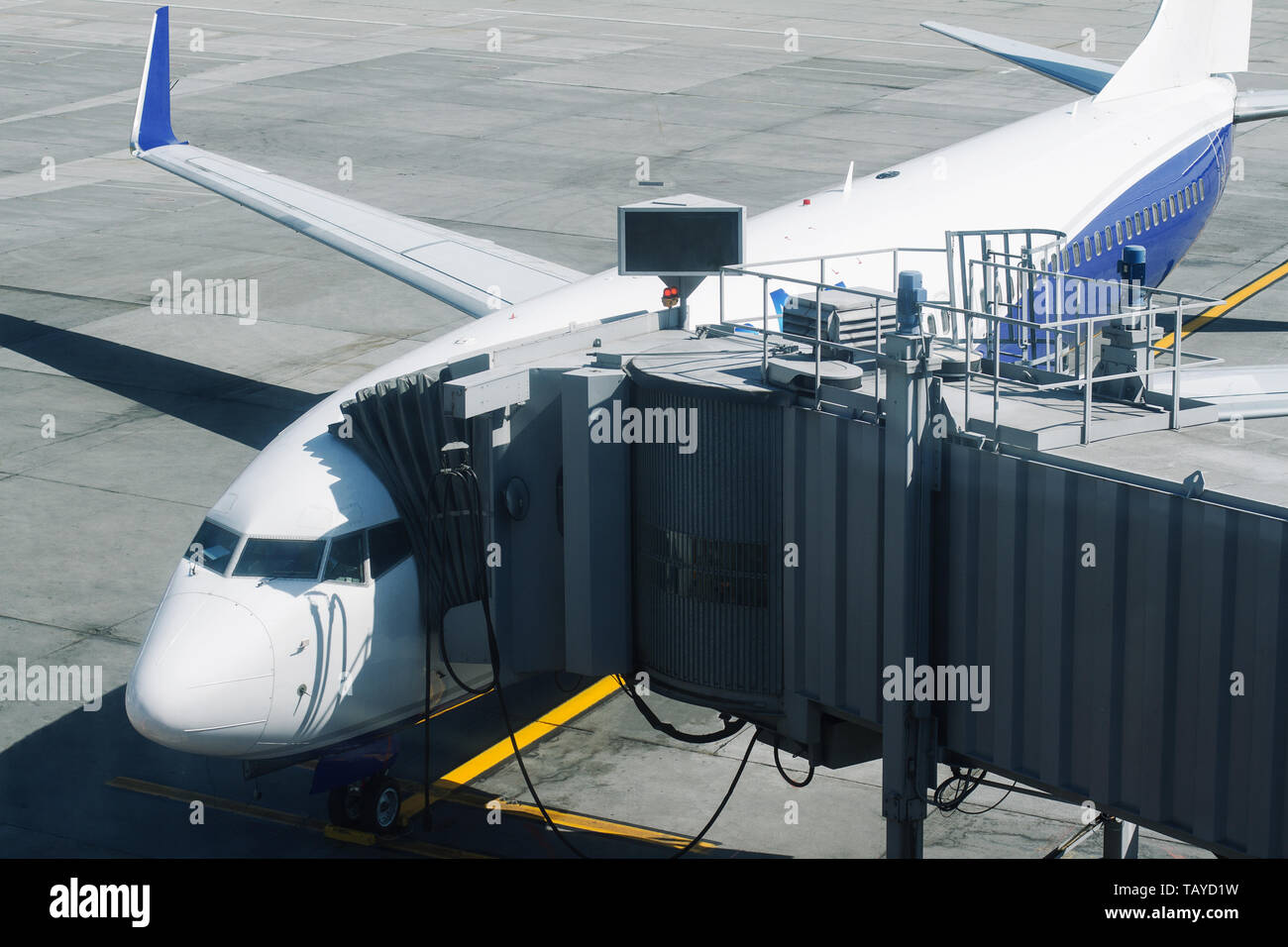 horizontal front view closeup of passenger plane with embarkation tunnel ready for take off on airport runway - Stock Image