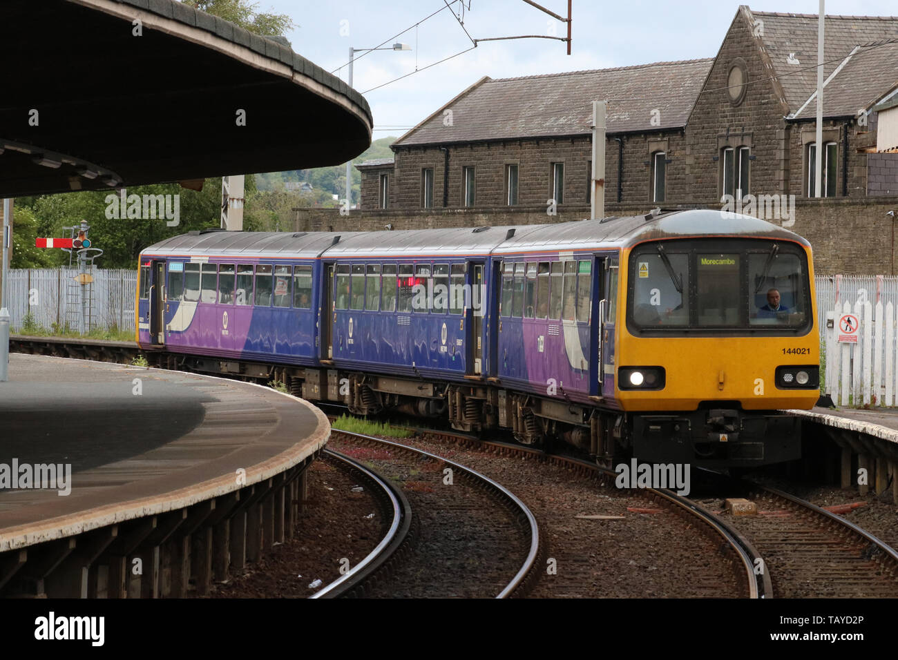 Class 144 pacer diesel multiple unit in Northern livery arriving at platform 1 at Carnforth railway station with passenger service on 27th May 2019. - Stock Image