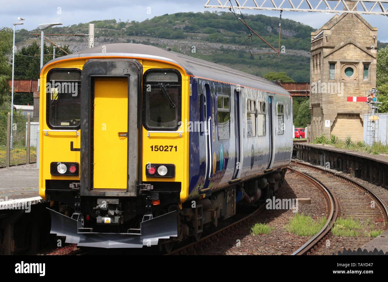 In gleaming new livery, Northern class 150 sprinter diesel multiple unit train leaving Carnforth station with a passenger service on 27th May 2019. - Stock Image