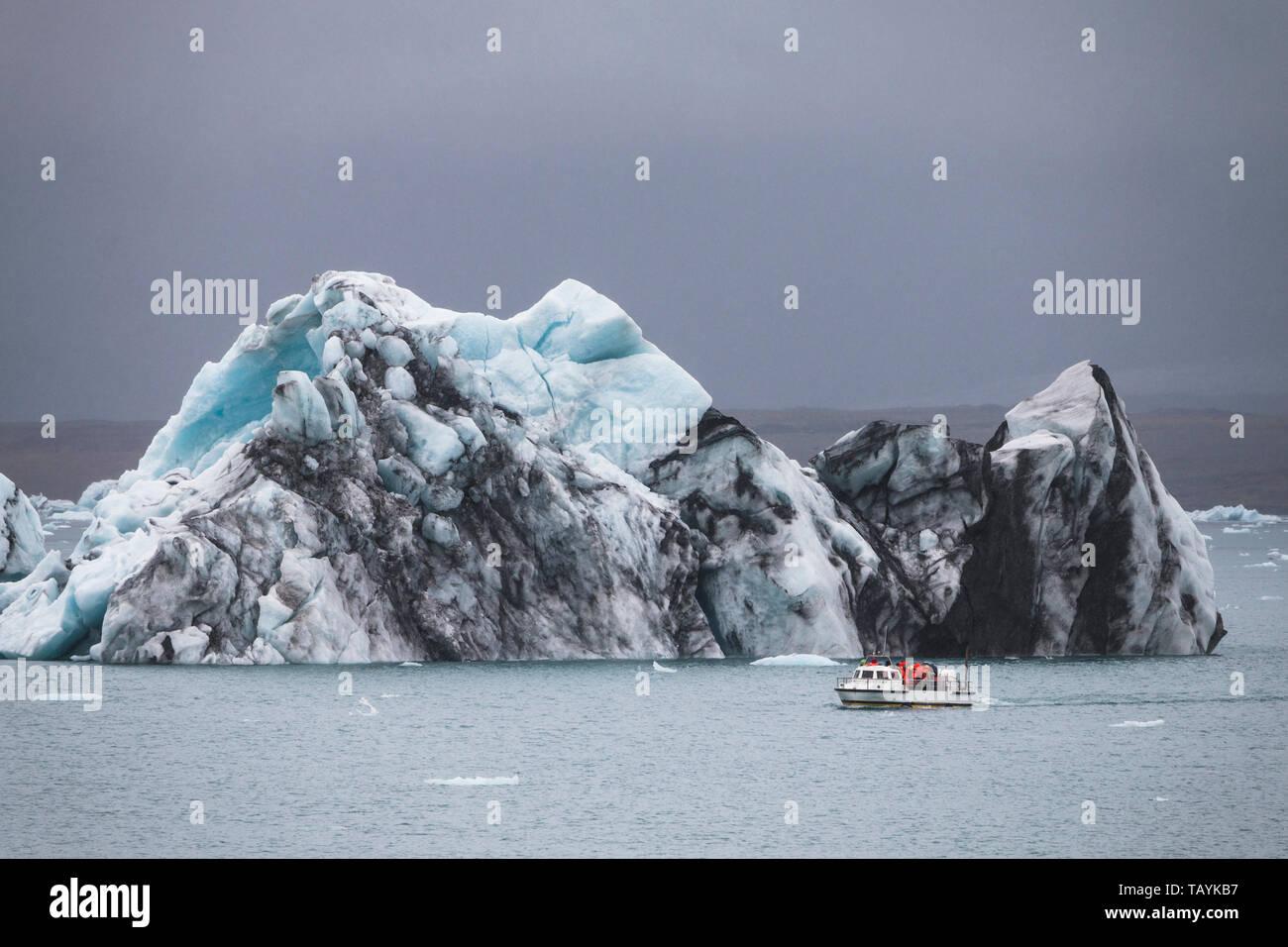 Huge iceberg and resque boat in Iceland Jokulsarlon Stock Photo