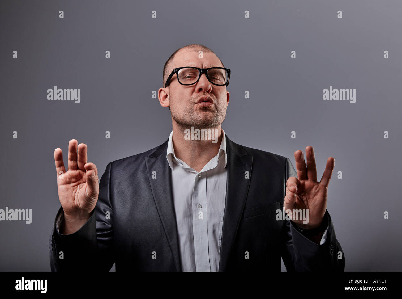 Grimacing comic bald business man in black fashion eyeglasses practicing the yoga and showing the zen sign on grey background. Closeup portait - Stock Image