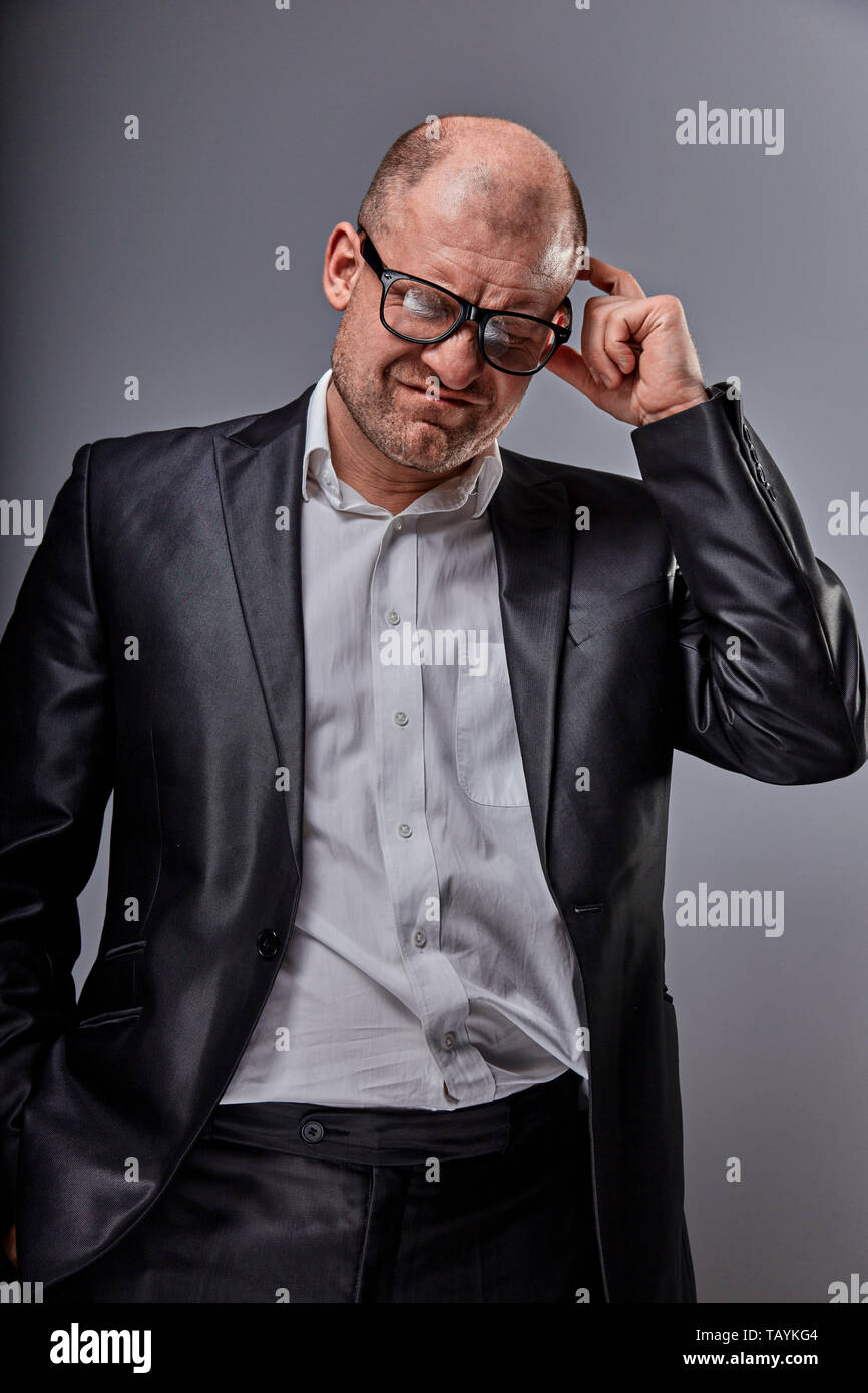 Depression bald business man in eyeglasses scratching the head in suit on grey background. Closeup studio portrait. - Stock Image