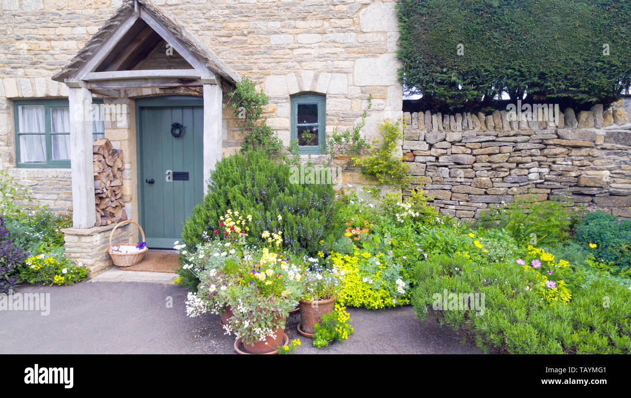 Front garden with vibrant flowers in bloom, lush herbs by a stone cottage in an english rural village. Stock Photo