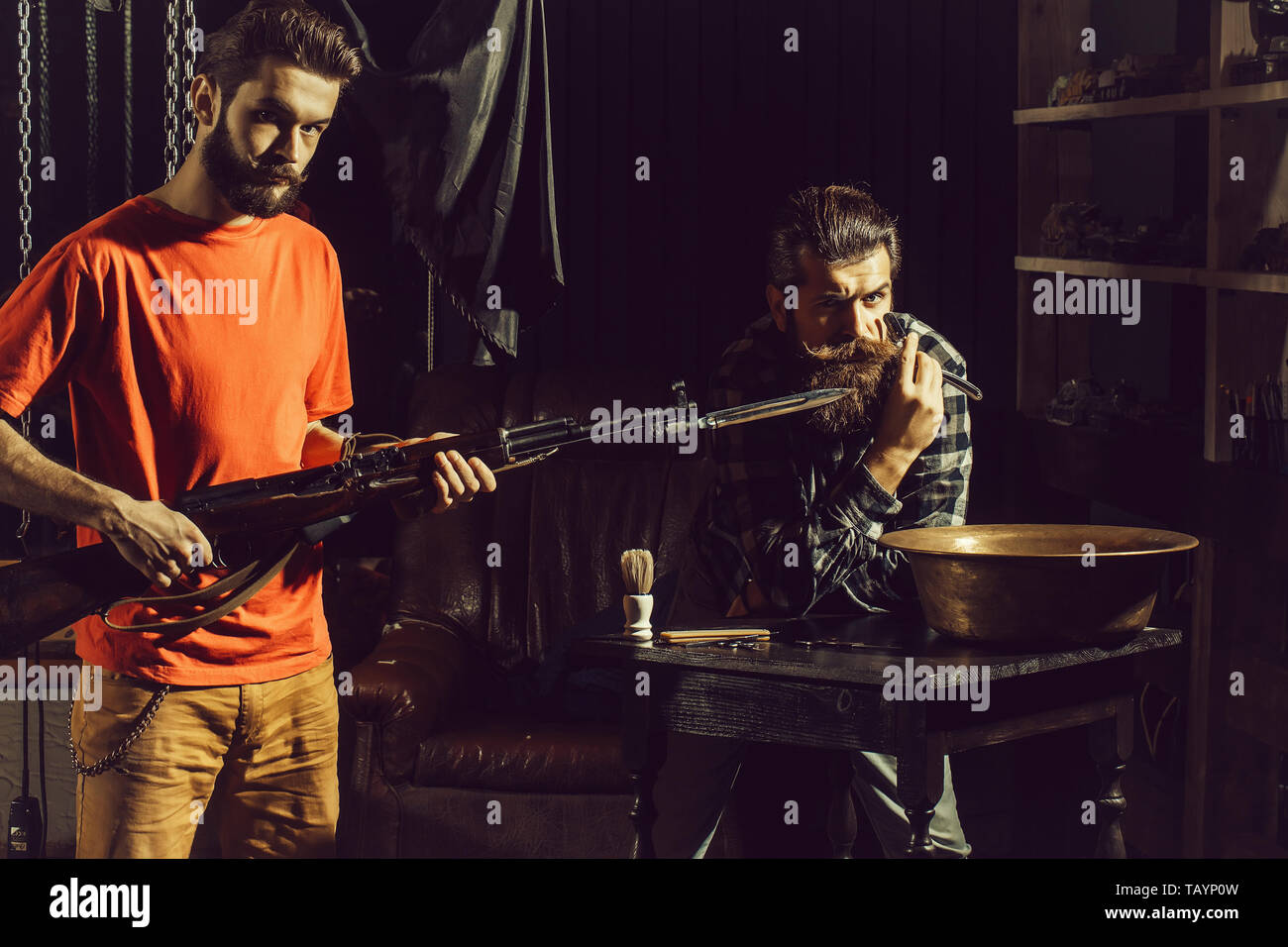 Two men, handsome, bearded hipsters, with beards and moustaches hold rifle with bayonet and razor with blade on dark background - Stock Image