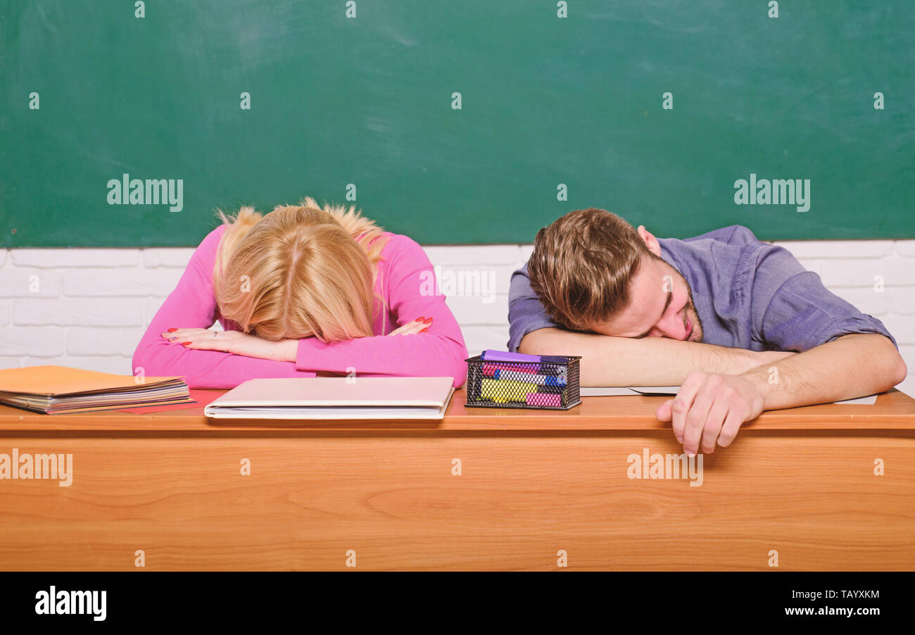Student life issues. Guy and girl tired or lazy student lean on desk in classroom. Feeling bored. Studying in college or university. Apply for free program. Couple friends student studying university. - Stock Image