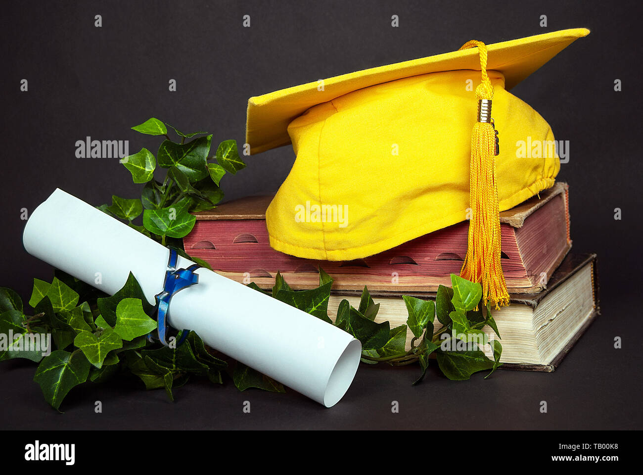bright gold graduation cap on old books with white blank diploma tied with blue ribbon - Stock Image