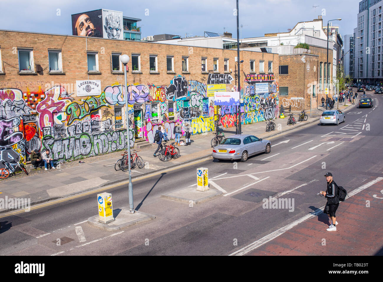 Shoreditch, London, England, UK - April 2019: Hipster man crossing the road on Bethnal Green Road near Shoreditch high street station and BOXPARK - Stock Image