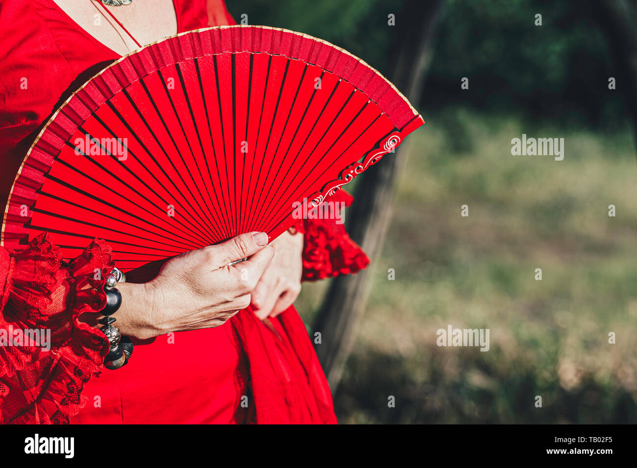 Woman in red dress with hand red open fan and bracelet, headless portrait - Stock Image