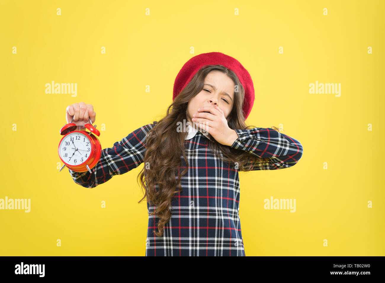 Its time to go to sleep. Sleepy little girl in evening time on yellow background. Yawning small child holding alarm clock. Late time. Break time, refresh yourself. - Stock Image
