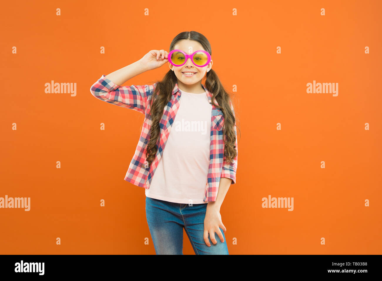 Look well and feel beautiful. Adorable girl with fashionable look on orange background. Little child having geeky look in fancy eyeglasses. Beauty look of small fashion model. - Stock Image