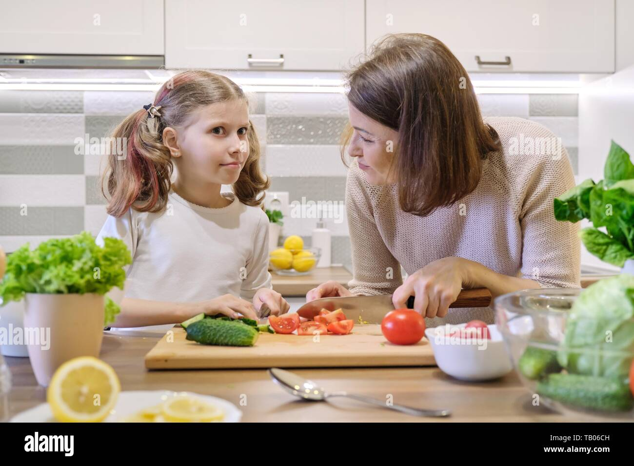Mother and daughter cooking together in kitchen vegetable