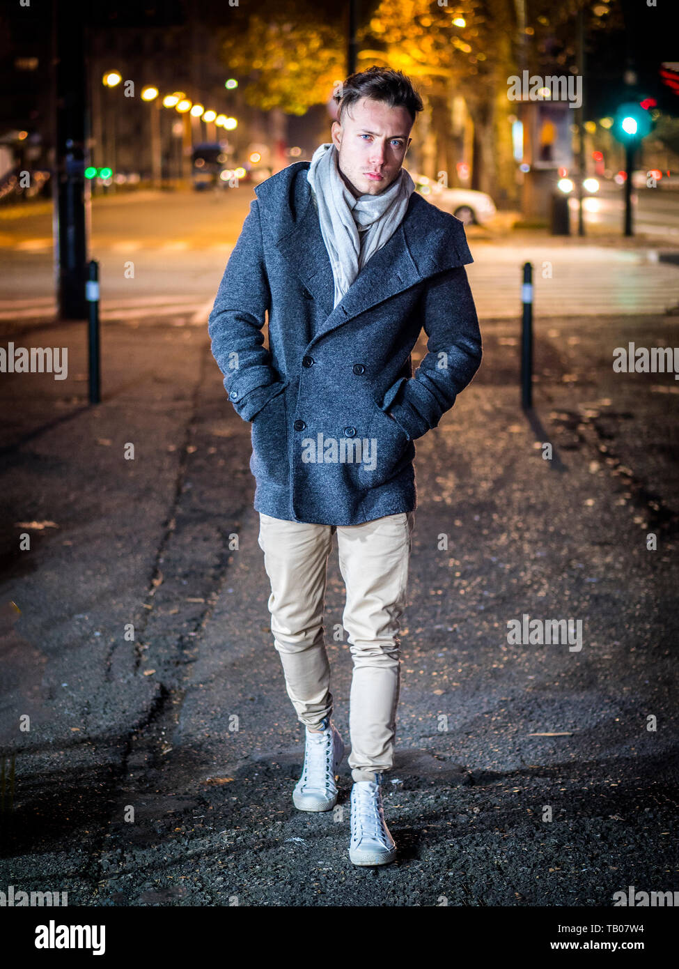 Handsome trendy young man, standing on a sidewalk at night Stock Photo
