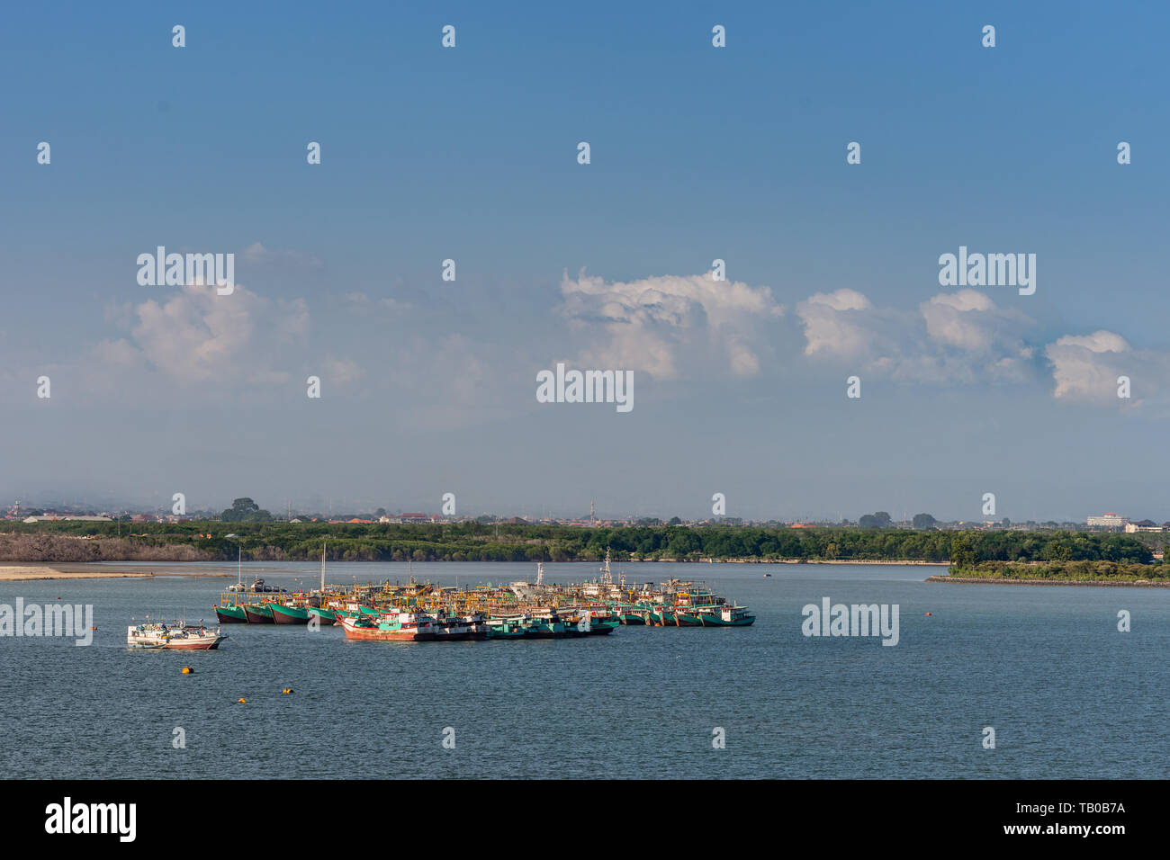 Benoa harbour, Bali, Indonesia - February 26, 2019: cluster of green and red fishing vessels anchored in middle of the port under evening light. Darke - Stock Image