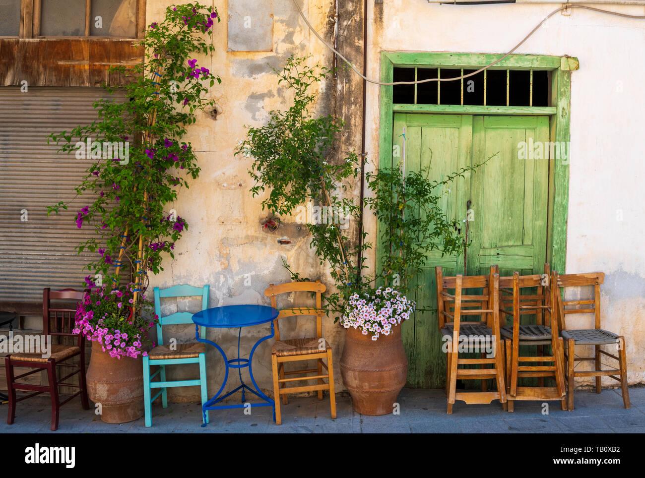 Stacked chairs outside Greek street cafe, Agio Nikolaos, Crete Stock Photo