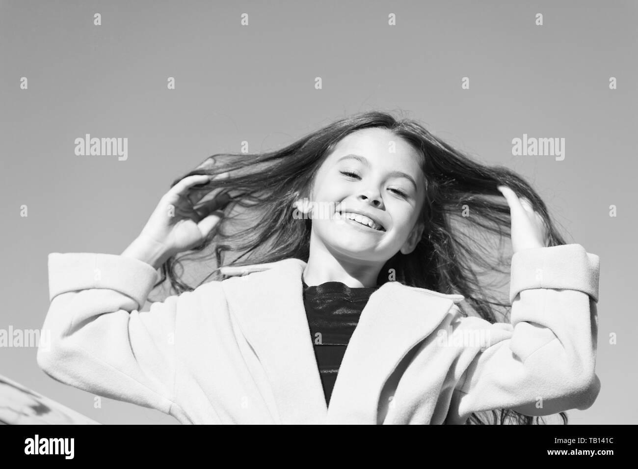 Happy day. Kid girl long hair enjoy walk sunny day blue sky background. Girl carefree childhood walk. Charming little stylish fashionable girl. Feeling free and happy. Little child enjoy sunny walk. Stock Photo