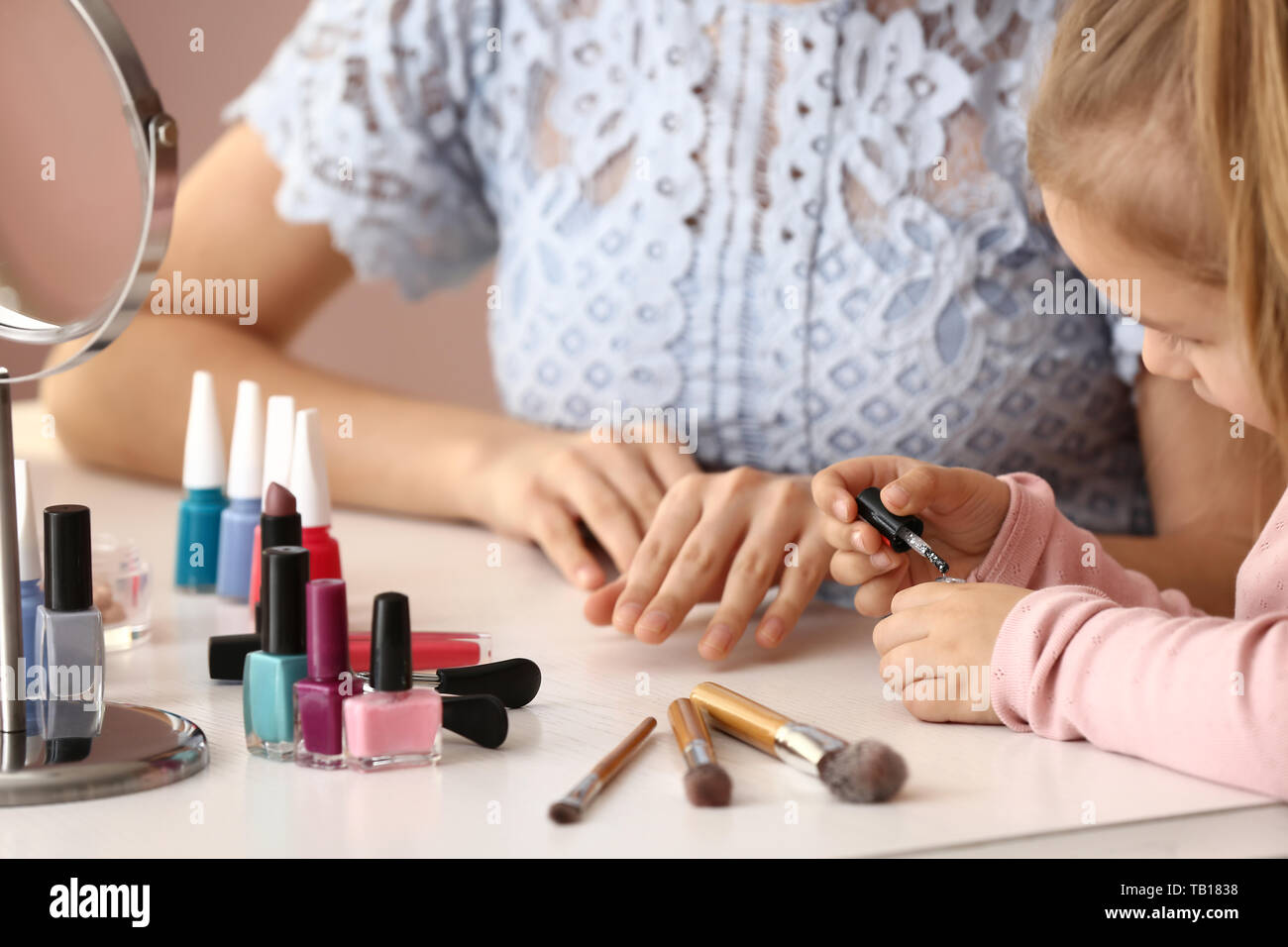 Cute daughter with mother making manicure at home Stock Photo