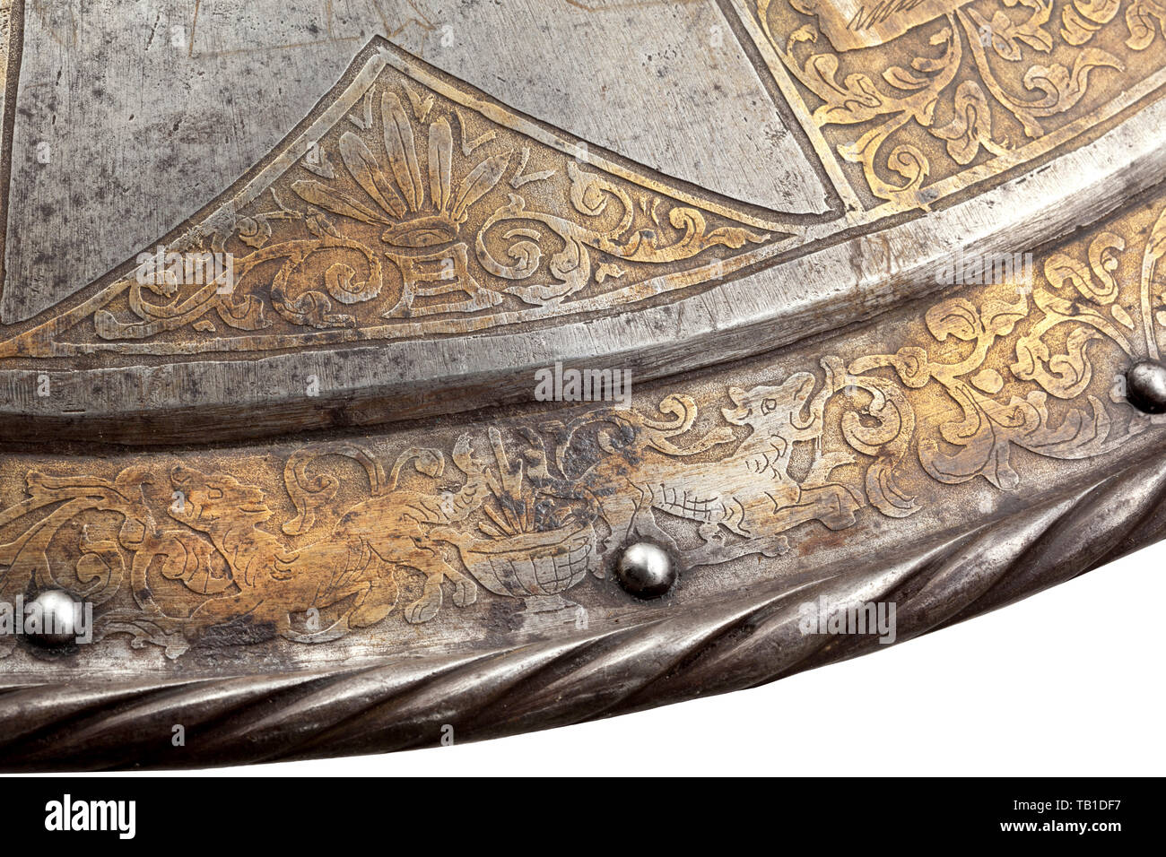 An etched and gilt iron parade shield inspired by the French or Flemish late 16th century style, 19th century, Convex, with recessed border and boldly turned and roped edge, fitted with central spike, studded with lining rivets and pairs of rivets for enarms (missing), decorated with radiating etched and gilt bands of foliage also enclosing a series of classical allegorical figures, and with an etched circular border frieze of scrollwork inhabited by fantastic birds and beasts from mythology. Diameter 61 cm. defensive arms, weapons, arms, weapon,, Additional-Rights-Clearance-Info-Not-Available - Stock Image