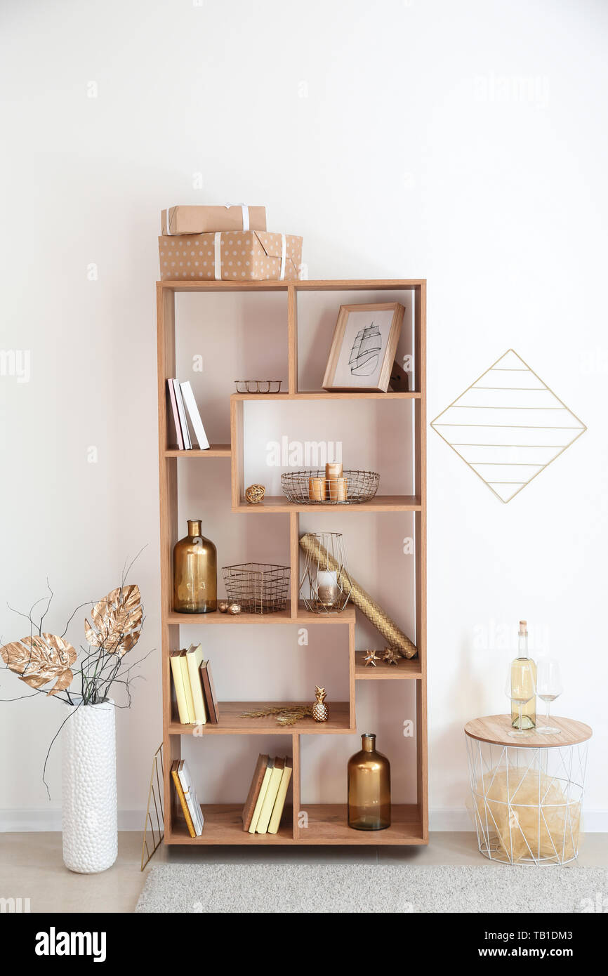 Wooden Shelving Unit With Golden Decor Near White Wall Stock Photo Alamy