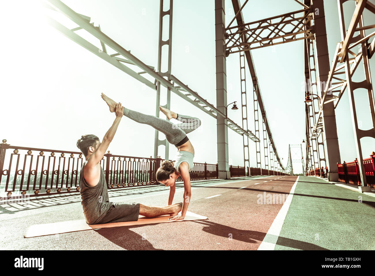 Dark-haired female yogi standing in a handstand pose - Stock Image