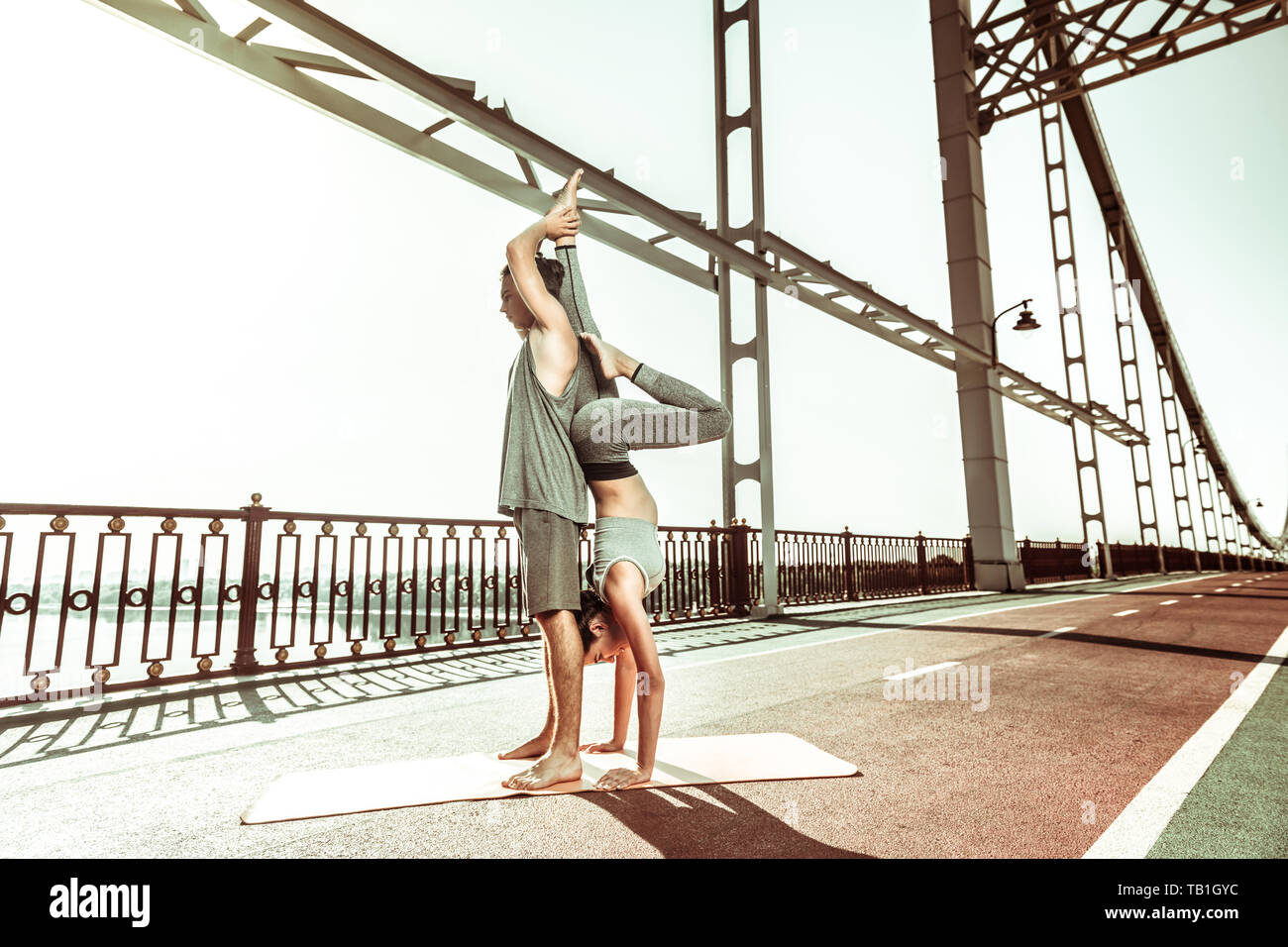 Slim woman practicing a candle stick asana assisted by her yoga partner - Stock Image