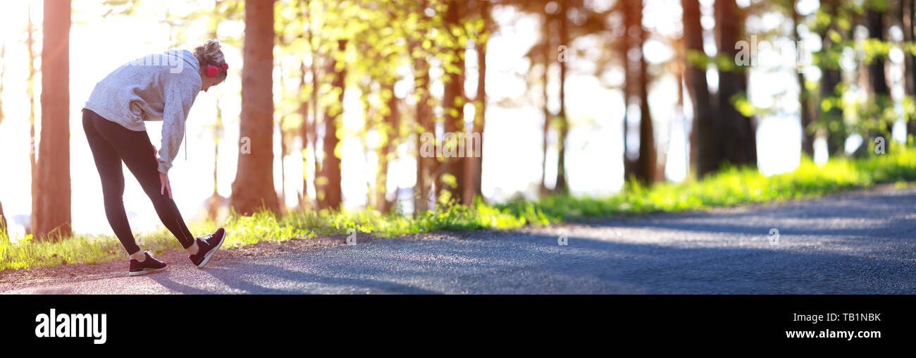 Young woman running in the park - Stock Image