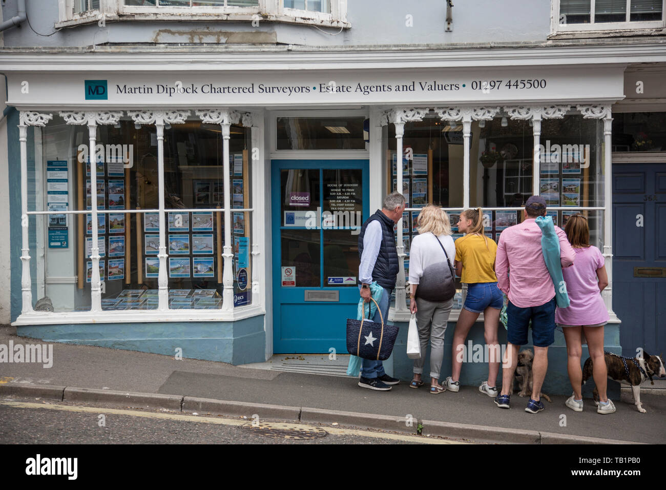 Family looking at properties for sale advertised in an estate agent window in West Dorset, England, United Kingdom Stock Photo
