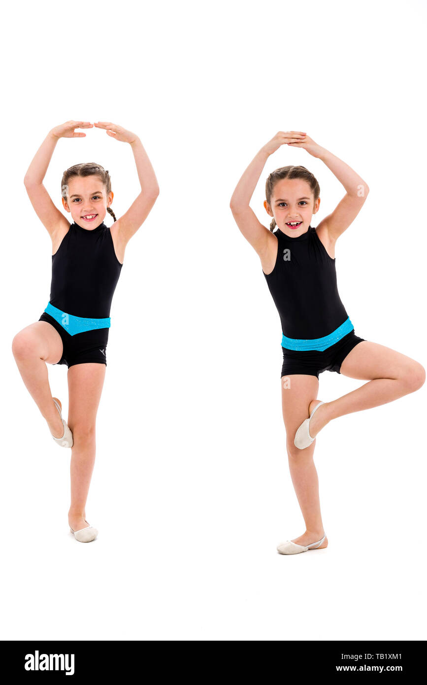 Identical twin girls practice and doing rhythmic gymnastics, white background. Young sister girls are dancing and having fun performing rhythmic gymna - Stock Image