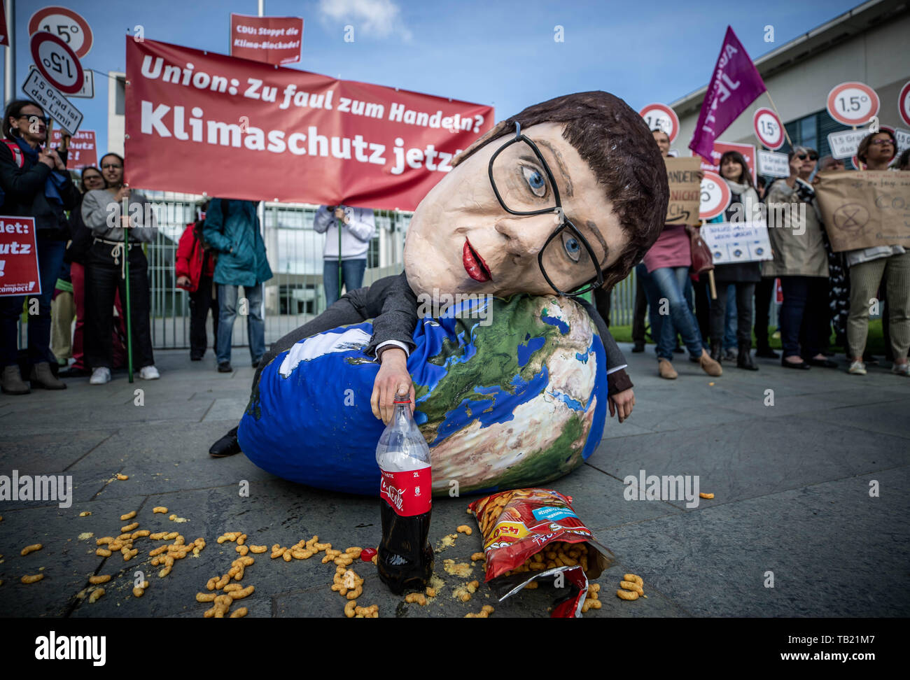 Berlin, Germany. 29th May, 2019. An activist from Campact, wearing a large mask, which CDU Chairwoman Annegret Kramp-Karrenbauer is supposed to depict, lies at a rally criticising the Union's lack of climate protection. The Climate Cabinet meets at the same time in the Chancellor's Office. Credit: Michael Kappeler/dpa/Alamy Live News Stock Photo