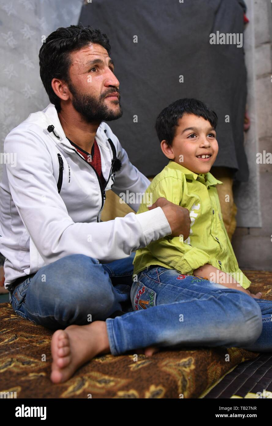 """Damascus, Syria. 28th May, 2019. Hussain Mossa (L) sits with his son Ibrahim in their unfinished house in the Jaramana suburb of Damascus, Syria, on May 28, 2019. For Hussain Mossa, whose childhood was peaceful and worth remembering, his son Ibrahim is not so lucky as him. Hussain's older son, Ibrahim, was born in 2011 when the Syrian crisis began. In Syria, those who were born during the war were regarded as """"Generation of War."""" They were unable to have a normal or healthy childhood like many of their parents did. Credit: Ammar Safarjalani/Xinhua/Alamy Live News Stock Photo"""